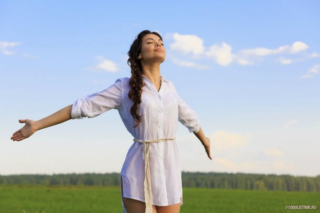 Девушка стоит в поле с раскинутыми руками