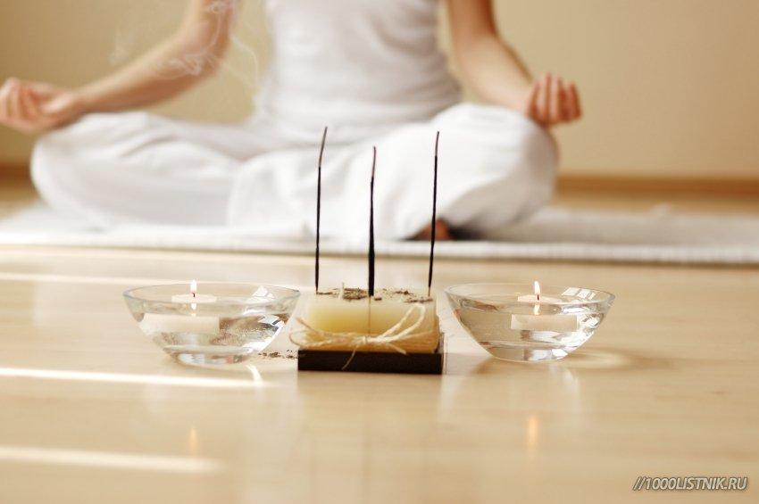Девушка медитирует с помощью ароматических палочек