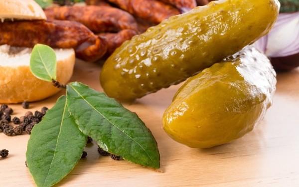 Солёные огурцы, хлеб и копчёное мясо