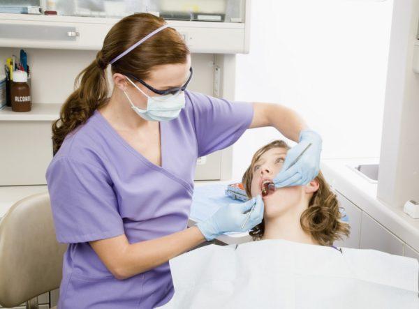 Девушка на осмотре у стоматолога