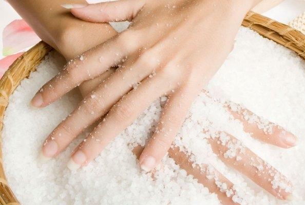 Женские руки в чашке с солью