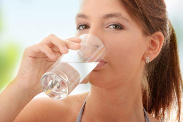 Девушка пьёт раствор соды