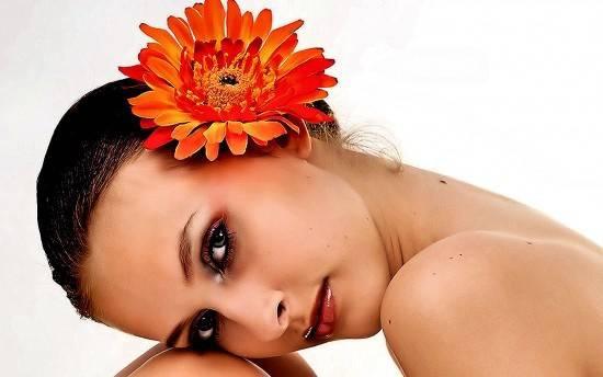 Красивая девушка с цветком календулы в волосах