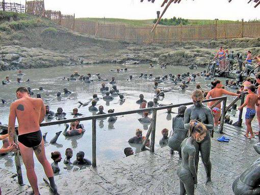 Люди принимают процедуры с глиной на курорте