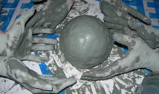 Руки держат шар из глины