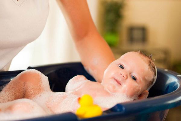 Женщина купает малыша