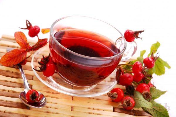 Чашка с лечебным чаем, ложечка и плоды шиповника