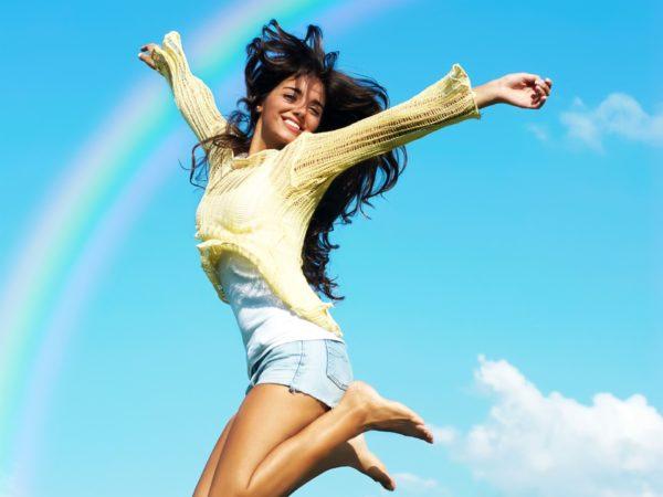 Девушка подпрыгивает на фоне ясного неба