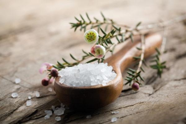 Морская соль в ложке и трава с цветком