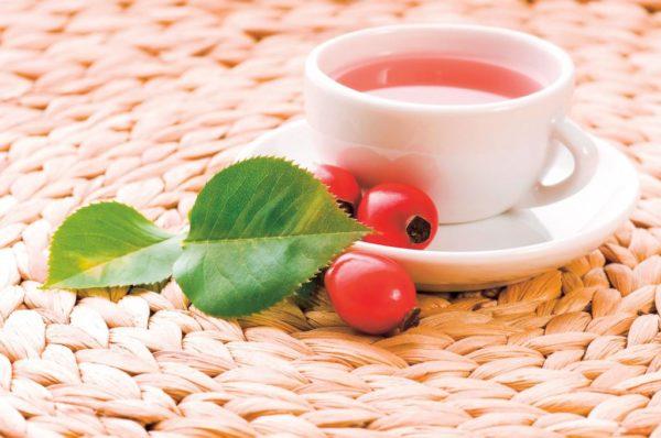 Плоды и отвар шиповника в чашке на столе