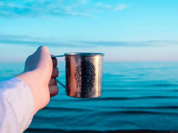 Рука с кружкой на фоне моря