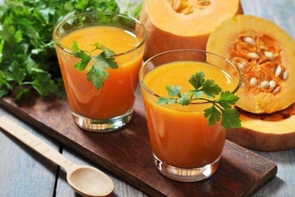 Два куска тыквы и два стакана сока с листиками петрушки
