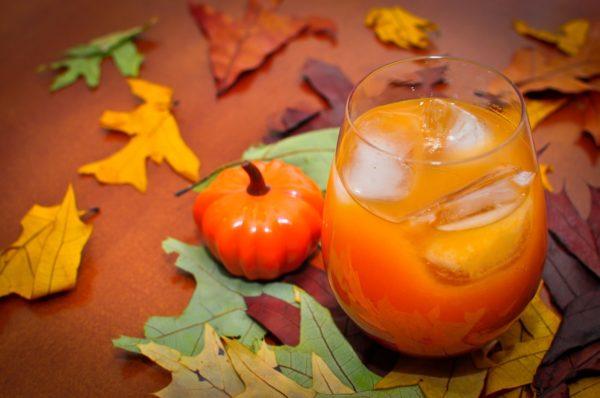 Тыквенный сок в стакане, пластмассовая тыквочка и осенние листья на столе