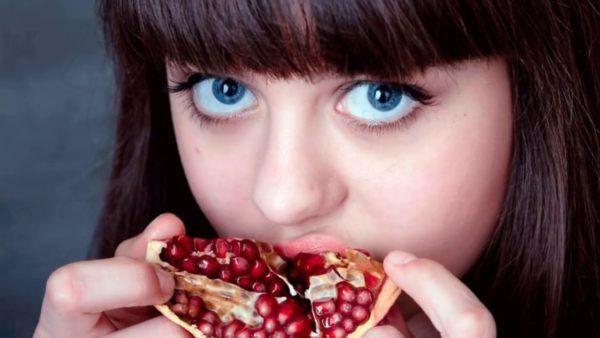 Девочка ест гранат