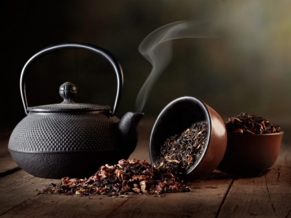 Тёмный керамический заварник и 2 коричневые ёмкости, наполненные сухим листом чёрного чая