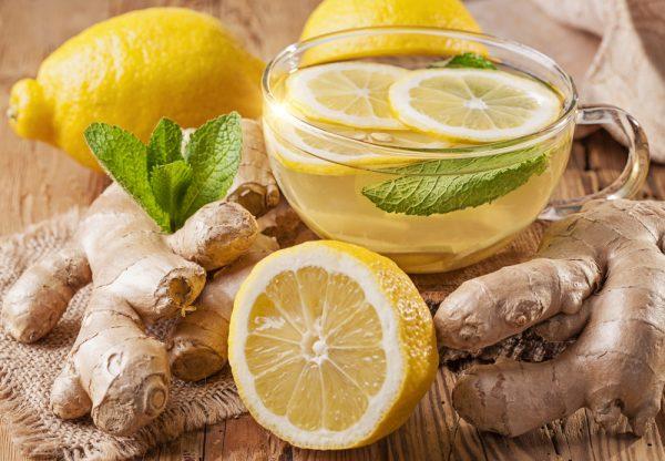 Корень имбиря, имбирный чай в прозрачной чашке, в которой плавает 2 кружка лимона и листик мяты, на заднем плане — лимоны