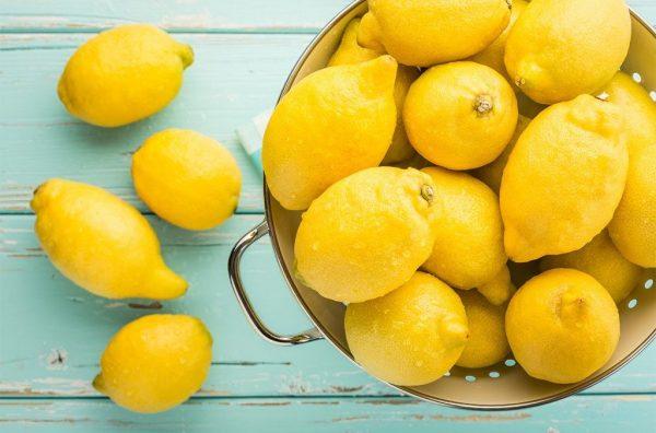 Лимоны в чашке и на столе