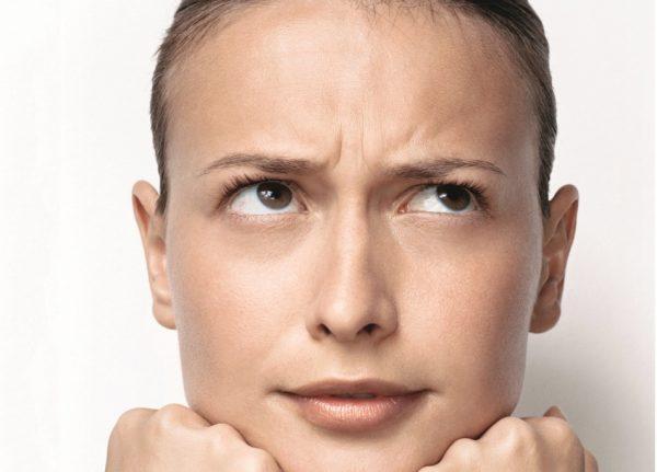 Девушка хмурится, в результате образуются морщины между бровей