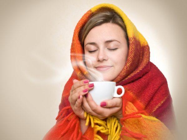 Девушка, укутанная в плед, пьёт чай