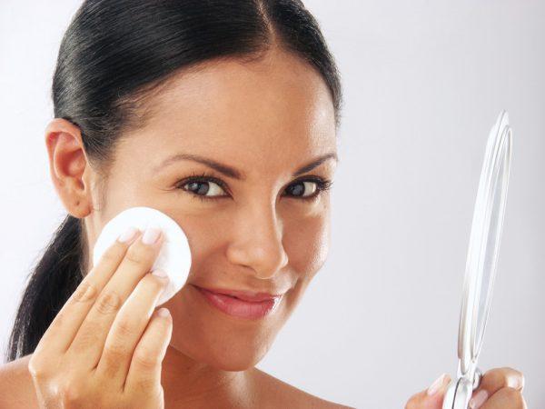 Девушка, держа зеркало, протирает лицо ватным диском