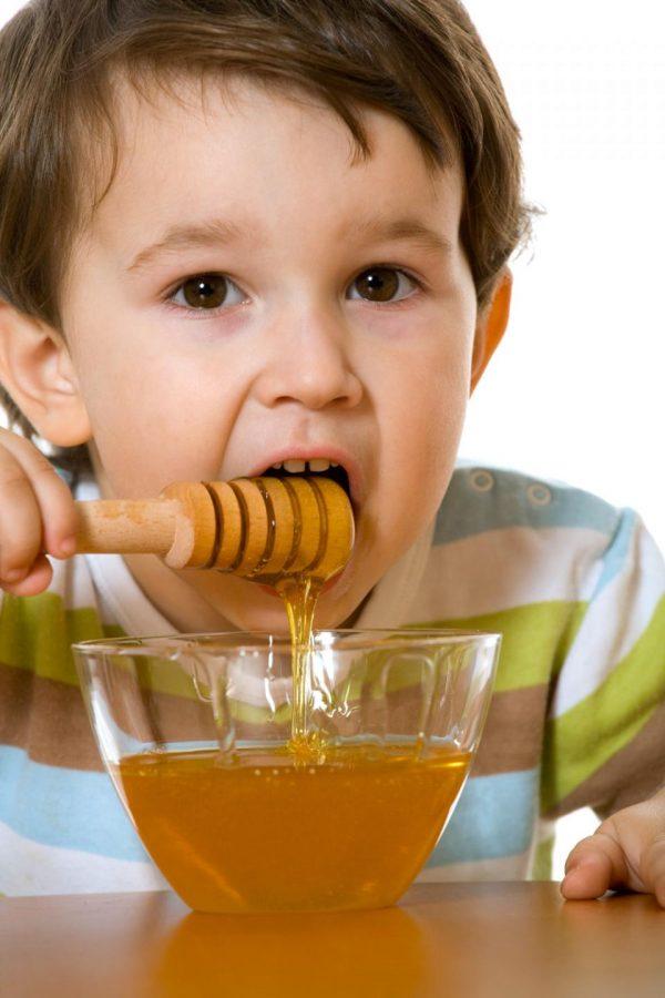 Ребёнок ест мёд