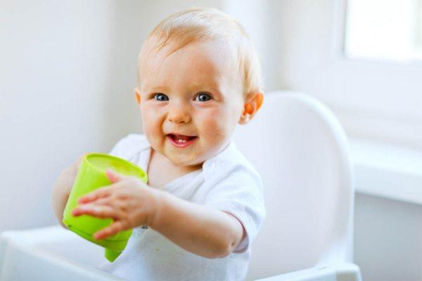 Улыбающийся ребёнок в белой футболке с зелёной чашкой
