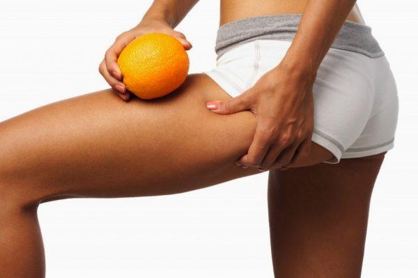 Девушка в белых шортах с апельсином в руке другой рукой сжимает кожу с внешней стороны бедра в попытках обнаружить целлюлит