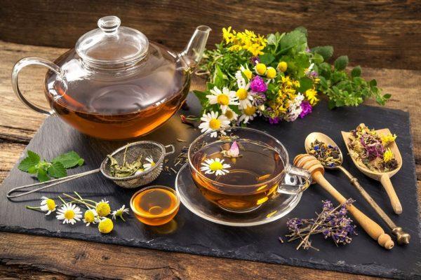 Стеклянный чайник, прозрачная чашка чая с плавающим цветком ромашки среди сухих и свежих трав, на переднем плане ситечко, пиала с мёдом, ложка, лопаточка для мёда и трав