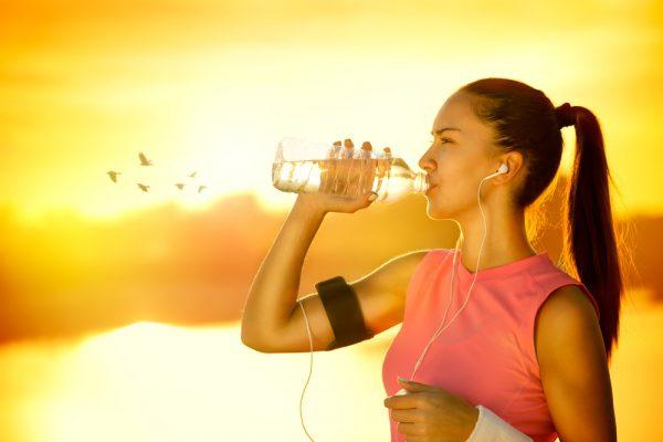 Девушка в розовой майке на фоне заката и стаи птиц пьёт воду из пластиковой бутылки, в ушах плеер