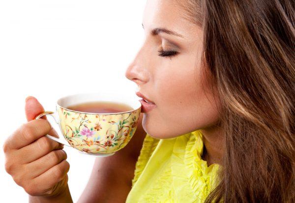 Девушка, закрыв глаза, с удовольствием пьёт чай из чашки в цветочек