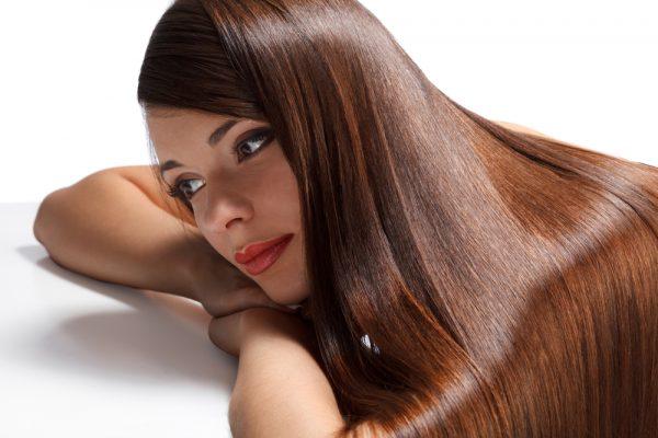 Девушка с красивыми блестящими каштановыми волосами прилегла на руки