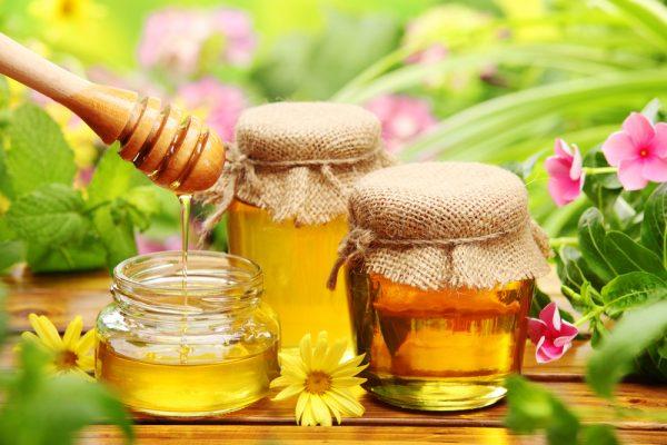Три баночки мёда, одна открыта и в неё стекает с палочки мёд, 2 из них завязаны кусочками мешковины на фоне зелени и цветов