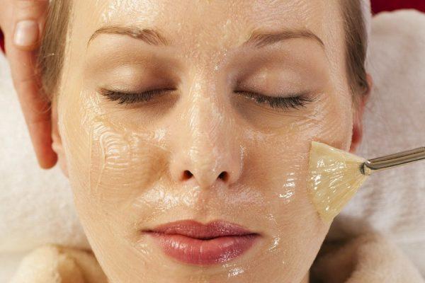 Девушке на лицо наносят кистью косметическую маску