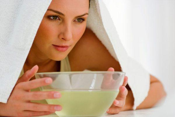 Девушка, накрытая белым полотенцем, склонилась над паровой ванночкой для лица