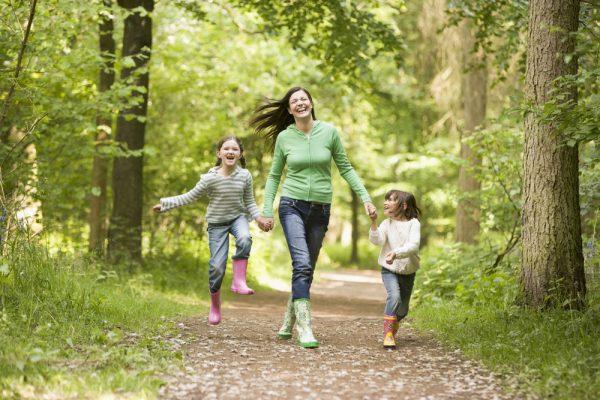 Счастливая женщина в зелёной кофточке и джинсах гуляет по дорожке парка с детьми