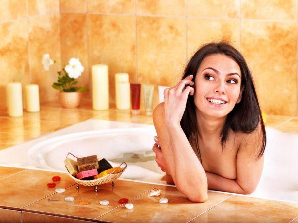 Симпатичная девушка улыбается, сидя в ванной, слева от неё вазочка с мылом, на заднем плане свечи и цветок в горшке