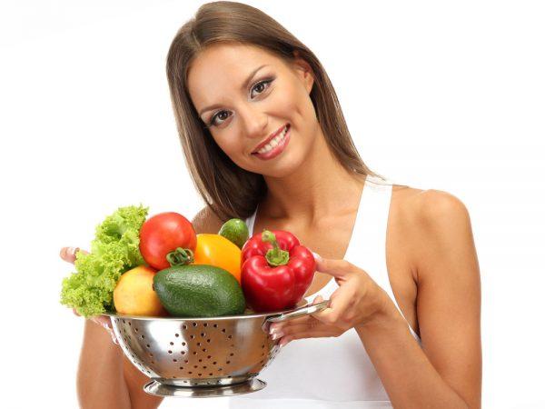 Девушка держит в руках овощи и фрукты