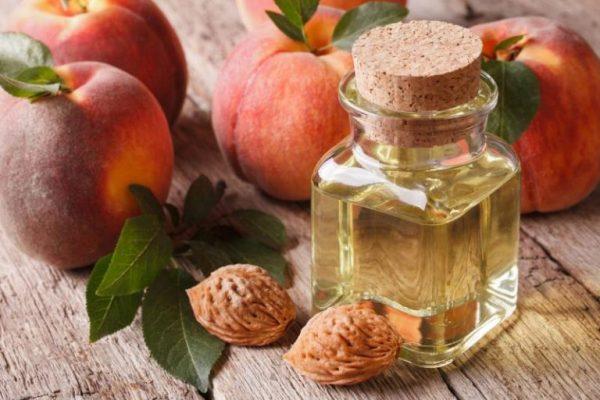 Персиковое масло и персики на столе